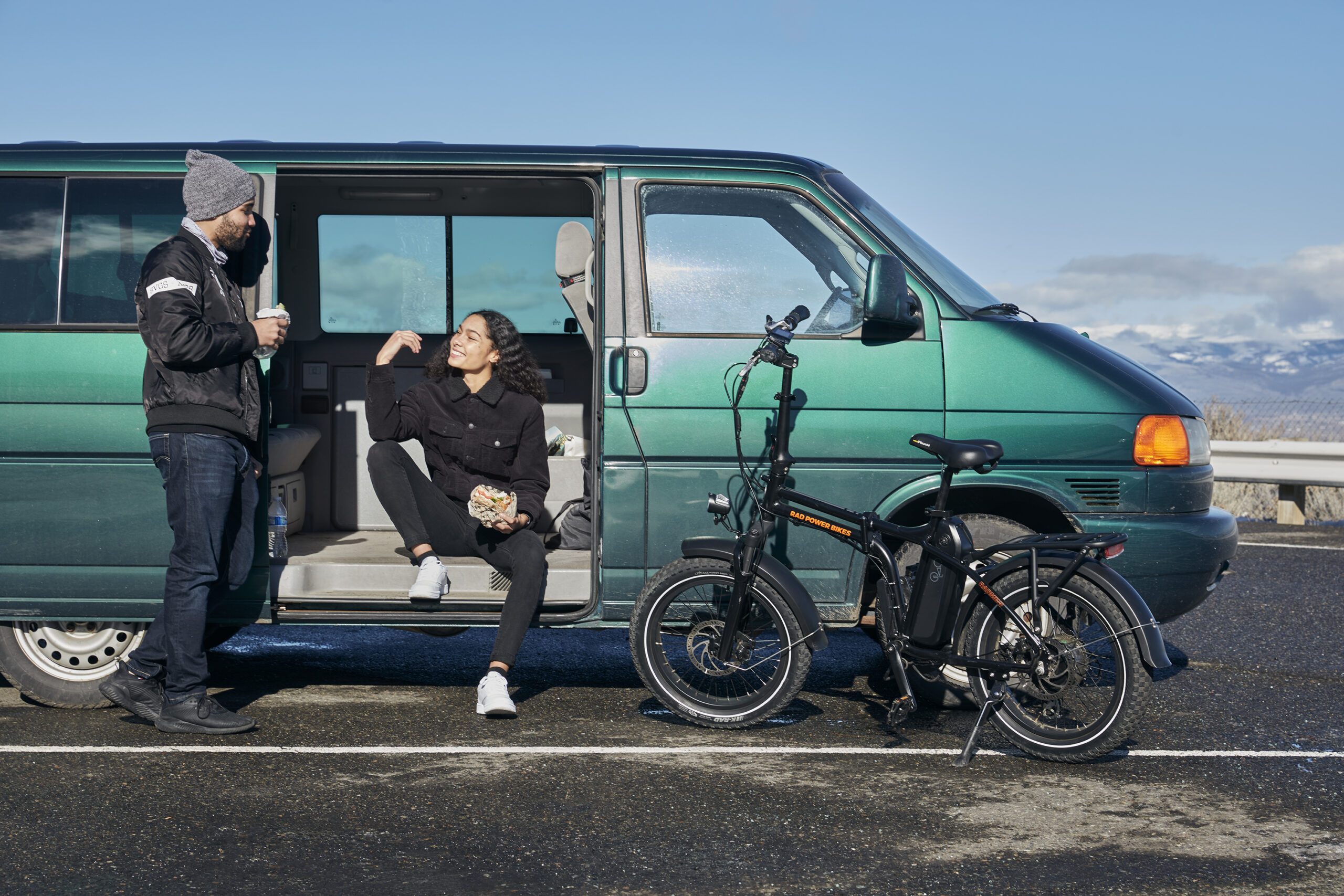 RadMini 4 Electric folding fat bike in front of a van on a beach