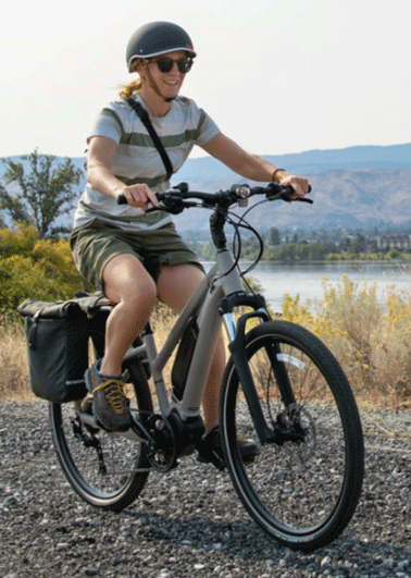 Woman with a helmet riding with an electric hybrid bike made by Co-op cycles